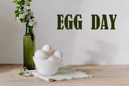 National egg day background with white eggs in bowl and flowers in green vase. National Egg Day on June 3 写真素材