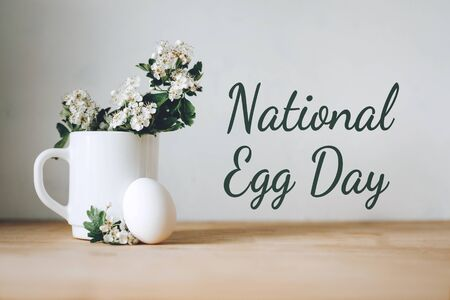 National egg day background with white eggs in bowl and flowers in green vase. National Egg Day on June 3 Stock Photo