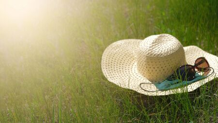Staycations, hyper-local travel, family outing, new normal concept. Straw hat, sunglasses and protective face mask against the background of rural landscape.