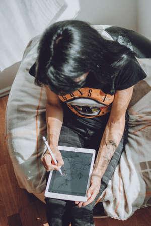 Tattoo art digital process on ipad. Tattoo artist working with Apple Pencil and drawing on iPad Pro in Procreate
