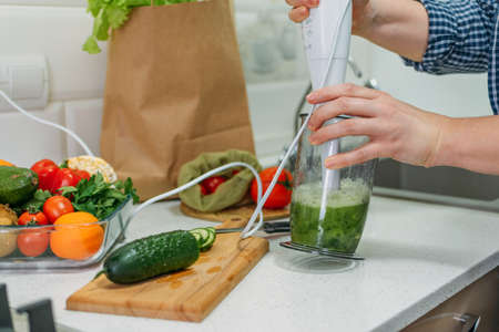 Green cucumber Smoothies for Weight Loss. Plus size woman making a cucumber cocktail. Female hand holding in hand glass with slimming Green Smoothie, juice 写真素材