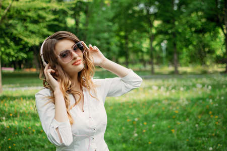Music for work, Concentration and relax. Young business woman in headphones enjoys music in city park, outdoor portrait of young business woman in headphones 写真素材