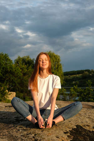 Relaxation, meditation mental health concept. National Relaxation Day. Red-haired woman meditates and relaxes in nature outdoor rocks