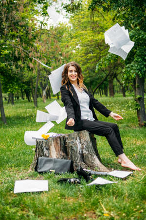 Out of office, dismissal, freelance, distant work, working remotely. Young business woman in suit sitting on grass in park throwing office documents and enjoys freedom