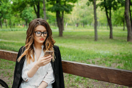 Starting a Business, startup, Outdoor Portrait of young business woman in glasses and with documents in a park. Beginner in own Business, Small Business Ideas