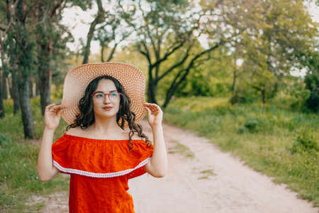 Local Domestic travel, green tourism . Summer time concept. Portrait of a beautiful woman in straw hat and red dress walking on rural road