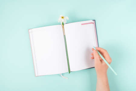 Self Care, wellbeing mockup with open notebook, flower narcissus and female hand. Beauty, self care routine