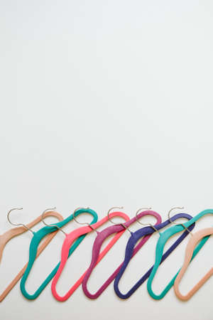 Sustainable responsible consumption concept. Many bright multi-colored velvet pop color hangers on white background. Store, sale, design, empty hanger.