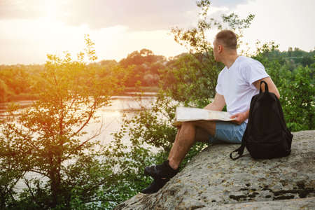 Solo traveler, planning a solo vacation, vacation in locations visit alone. Man tourist sitting on a stone by the river read the map. 写真素材