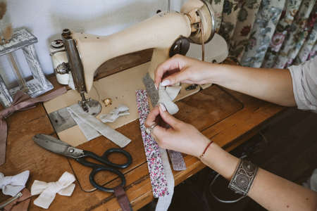 Small business ideas, seamstress local business, vintage dressmaker workspace. Old vintage hand sewing machine, Ribbons, spools of thread, sewing accessories on a wooden table