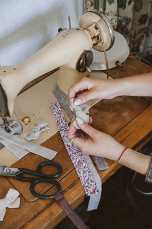 Small business ideas, seamstress local business, vintage dressmaker workspace. Female fashion designer making craft fabric hair accessories, bow, hairpins. Tailor working at desk with sewing machine.