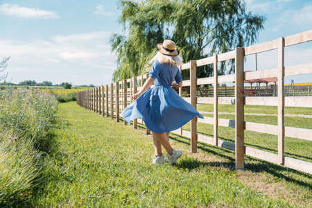 Cottagecore Farmcore Countrycore aesthetics, fresh air, countryside, slow life, pastoral life, outdoor picnics, wearing grandma clothes. Young girl in straw hat with flowers walks on country farm. Stockfoto