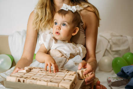 Little girl playing with wooden ABC blocks. Plastic-free wooden zero waste kids toys for safe and sustainable gifting. Eco friendly, plastic free toys for toddler