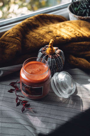Work-life balance, cosy at home, relaxing indoors concept. Winter fall cozy mood concept. Still life details with Scented Aromatherapy Candle, cacao and cup and knitted sweater Stockfoto
