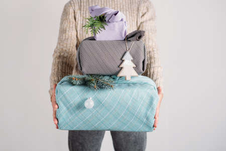 Holiday gifts christmas background with many Furoshiki gift boxes wrapping in zero waste style. Many Furoshiki gift boxes in female hands Christmas web banner.