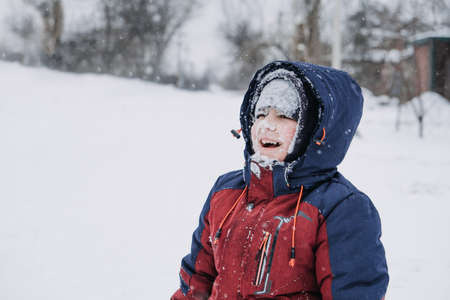 Close up outdoor winter portrait of boy face in the snow. Authentic, real, candid portrait of cute boy in winter time. Little kid in winter clothes walking under the snow