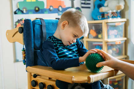 Sensory Activities for kids with disabilities. Preschool Activities for Children with Special Needs. Boy with with Cerebral Palsy in special chair play with mom at home.