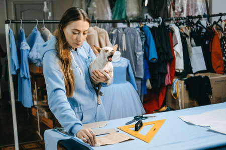 Small business, fashion designer, Tailor working, dressmaker workplace. Candid portrait of fashion designer creating outfit, tailor sews dress on the table.