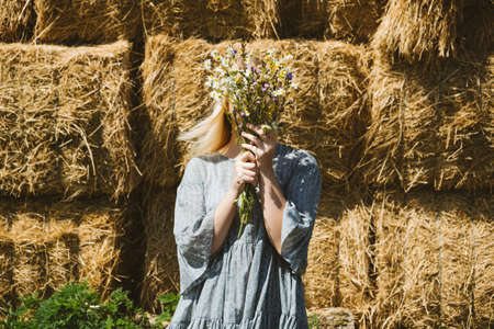 Cottagecore Farmcore Countrycore aesthetics, fresh air, countryside, slow life, pastoral life, outdoor picnics, wearing grandma clothes. Young girl in cotton dress with flowers walks on country farm