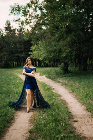 Party graduation prom fairytale concept. Beautiful brunette young woman in blue prom dress on nature background. Outdoor romantic portrait of brunette Latina Hispanic girl in long evening dress