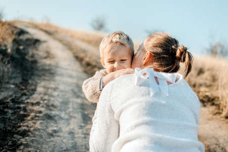 Mothers Day, celebrates motherhood, holiday in honor of mothers. Little boy kid son runing into the arms of his mother in nature background. Selective focus Stok Fotoğraf