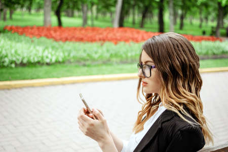 Outdoor portrait of young businesswoman with cell phone on nature background. Smartphone in hand business woman in formal suit.