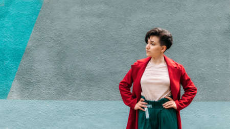 Candid portrait Young Brunette woman with short hair on blue wall background. Outdoor portrait modern gen z woman in red coat