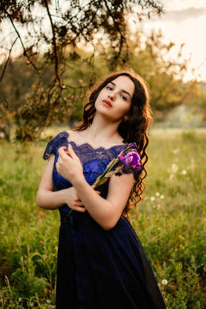 Party graduation prom fairytale concept. Beautiful brunette young woman in blue prom dress with iris flower on nature background. Outdoor romantic portrait of brunette girl in long evening dress