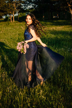 Party graduation prom fairytale concept. Beautiful brunette young woman in blue prom dress with lilac bouquet on nature background. Outdoor romantic portrait of brunette girl in long evening dress