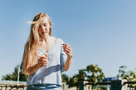 Outdoor lifestyle portrait of young trendy girl eating ice cream in summer hot sunny day in street city