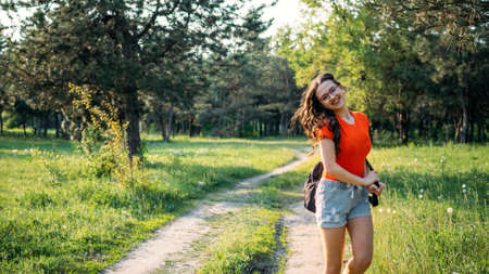 Local travel, Rural tourism, Staycations, gen z traveler, Young Adventurer, Solo Travel. Back view of Young brunette woman with backpack walking on country road to forest