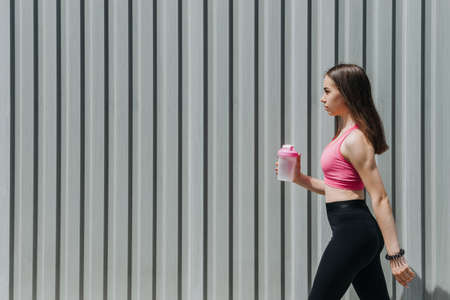 Sports and Hydration, Drink water, Stay Hydrated During Exercise. Fitness young woman, teen girl drinking water after outdoor running workout in sun summer day