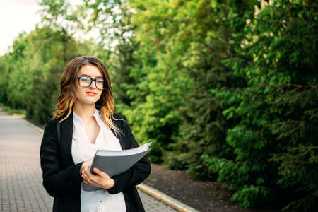Young business professionals, gen z woman working, first job, interns, internship. Candid portrait Young business woman in formal suit and with documents on nature green background