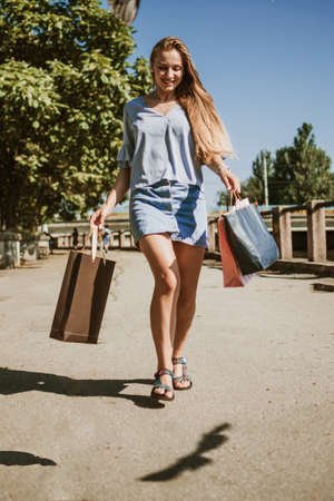 Spring summer sale, enjoys shopping, consumerism. Happy young woman with many shopping bags enjoying in shopping summer day.