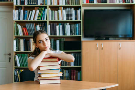 Back to school, reading book, education, library concept. Student girl with book on background of bookshelves in the library.