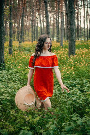 Enjoying the nature, wellness, wellbeing, healthy lifestyle, slow living. Young brunette girl in red dress and straw hat walking in forest, woods.