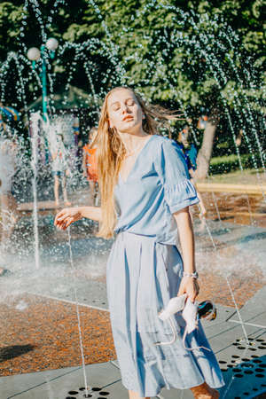 Hot summer, Keeping cool in the heat. Young woman in blue dress in water spray in city park fountain. What to wear on hot day