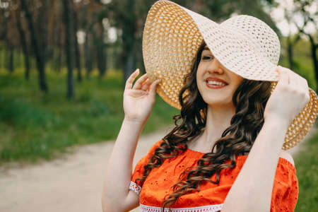 Summer skin hair care, natural beauty, Summer time. Young brunette woman with curly hair in straw hat on nature background. Teen girl in red dress walking in the country