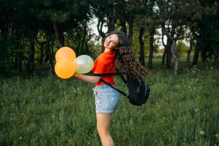 Summer vacation, school College break in summer, students get time off, Academic year end. Young brunette teen girl with backpack and colorful balloons enjoying the summer Stok Fotoğraf