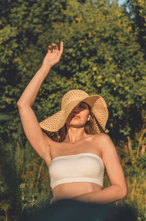 Sun Protection, sunscreen , UV protection, Time Outside and Stay Sun-safe. Young woman with straw hat protects from sun and enjoying nature