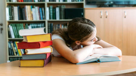 College Students overwhelmed, overworked, burned out, perfectionists. Teen tired girl, young woman sitting at table with books in college library