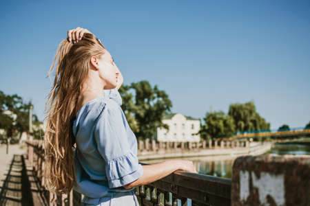Summer Hair Care, Sunscreen for Hair, Conditioning. Blonde girl with long hair stands near river in the city in summer day
