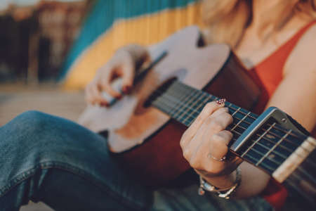 Creative hobbies, guitar lessons, playing musical instruments. Acoustic guitars for beginners. Young blonde woman with Acoustic guitar outdoor Stok Fotoğraf