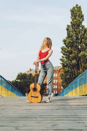 Young Musicians, aspiring musicians, young professional artists, music performing, composer. Young blonde woman with Acoustic guitar outdoor