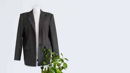 Sustainable fashion, organic clothes, eco clothing, ecology, sustainability, responsible fashion, 100 cotton. Formal Bio fabric suit with green plants on light background.