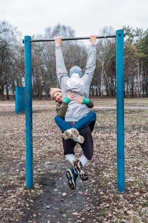 Outdoor Pull-up Bar and Parallel Bars workout. Socially distant bootcamps. Group fitness workout classes outdoors in public parks. Woman and man training together. Health, wellness and community 免版税图像