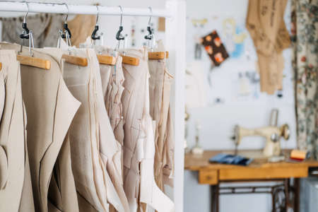 Many paper sewing patterns for different clothes hanging on the rack in sewing factory background. Clothing pattern, manufacture on sewing factory. Tailoring, small business 免版税图像