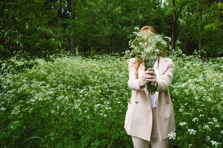Mental Health Awareness Month, behavioral health care. Post COVID-19 pandemic mental health challenges. Red-haired young woman on green nature trees and flowers background 免版税图像