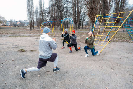 Group fitness workout classes outdoors. Socially Distant Outdoor Workout Classes in public parks. Three women and man training together in the public park. Health, wellness and community concept