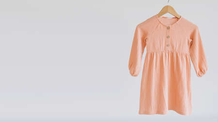Muslin Eco Friendly Clothing, Organic Muslin Clothes. Natural tones dresses on beige recycled cardboard background